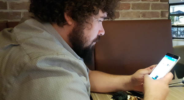 Man at table looking at mobile phone
