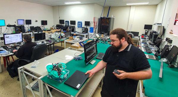 Technician finishing replacement laptop battery in Port Macquarie Computer Repair Shop